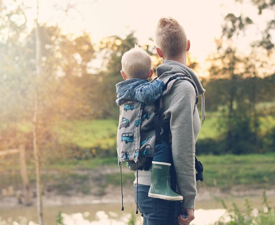 Het dragen van je kind in een drager of draagdoek.